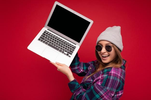 Seitenprofilfoto des lachenden verrückten schönen lächelnden dunkelblonden jungen frau, der computer hält