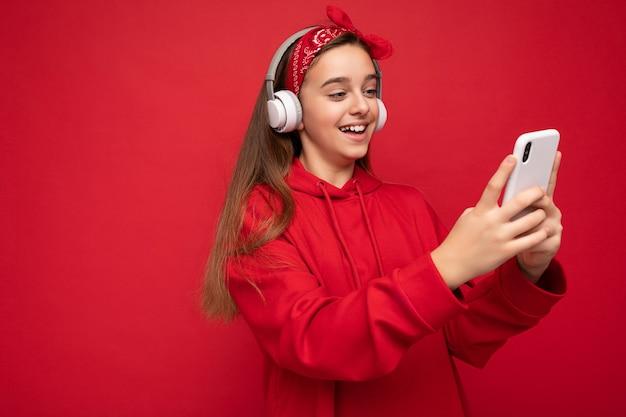 Seitenprofilfoto des lächelnden positiven attraktiven brünetten mädchens mit rotem hoodie isoliert auf rot
