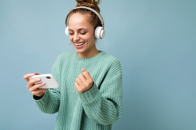Seitenprofilfoto einer attraktiven emotional positiven jungen frau, die einen blauen pullover trägt, isoliert über