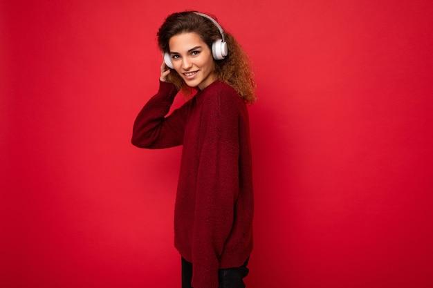 Seitenprofilfoto einer attraktiven, positiven jungen, braunhaarigen, lockigen frau, die einen dunkelroten pullover trägt, isoliert