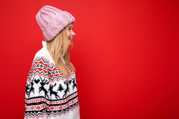 Seitenprofilfoto einer hübschen lächelnden, glücklichen jungen blonden frau, die isoliert über einer bunten hintergrundwand steht und alltägliche trendige kleidung trägt, die zur seite schaut. freiraum