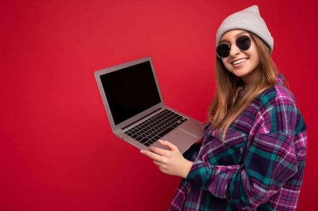 Seitenprofilfoto einer schönen lächelnden, glücklichen jungen frau, die einen computer mit lässigem smart hält