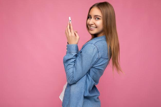 Seitenprofilfoto einer schönen lächelnden positiven jungen blonden frau, die ein lässiges blaues jeanshemd trägt