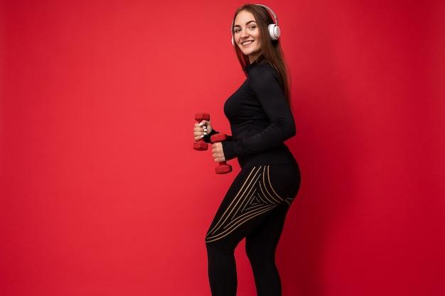 Seitenprofilfoto einer sexy attraktiven, positiv lächelnden jungen brünetten frau, die schwarzen sport trägt