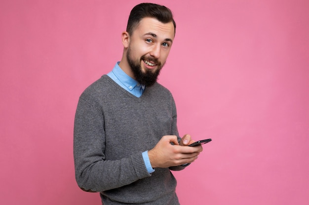 Seitenprofilfoto eines coolen, gut aussehenden, unrasierten jungen mannes mit bart in grau