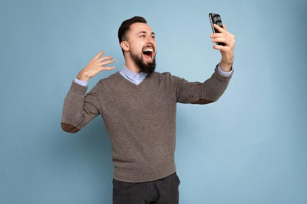 Seitenprofilfoto eines positiven, gutaussehenden jungen, brünetten, unrasierten mannes mit bart in lässigem grau
