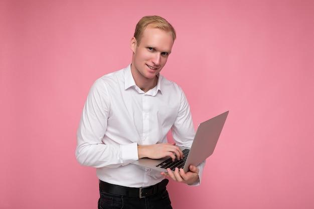 Seitenprofilfotoaufnahme des hübschen zuversichtlichen blonden mannes, der computer-laptop hält, der auf tastatur tippt, die weißes hemd trägt, das kamera lokalisiert über rosa hintergrund betrachtet.