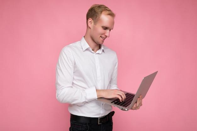 Seitenprofilfotoaufnahme eines gutaussehenden, selbstbewussten blonden jungen mannes, der einen computer-laptop hält und auf der tastatur tippt und ein weißes hemd trägt und auf den netbook-monitor schaut, der auf rosafarbenem hintergrund isoliert ist.