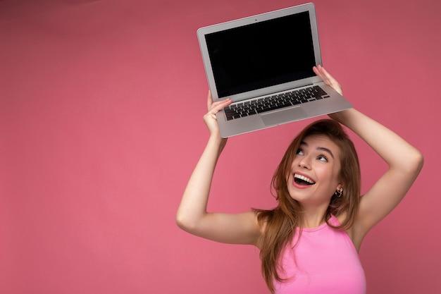 Seitenprofilporträt der überglücklichen schönen lächelnden glücklichen jungen frau, die computerlaptop hält