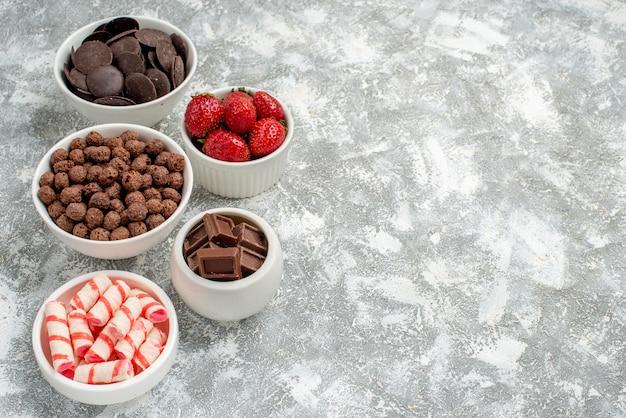 Seitenschalen oben links mit weiß-roten bonbons, erdbeeren, pralinen, müsli und kakao auf grauweißem grund
