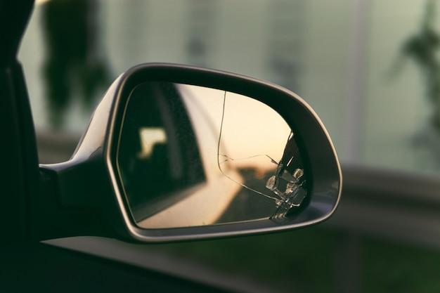 Seitenspiegel des autos mit blick zurück. broken spiegel hautnah.