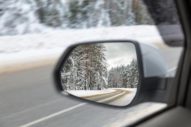 Seitenspiegelspiegelreflexion der schneebedeckten straße im wald