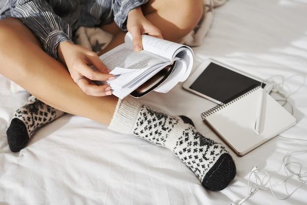 Seitenwinkelaufnahme der frau, die mit gekreuzten händen auf bett sitzt, ausgefallene socken trägt und notizen macht, während sie zu hause studiert. schüler arbeiten an hausaufgaben, verwenden ein digitales tablet und hören musik mit kopfhörern