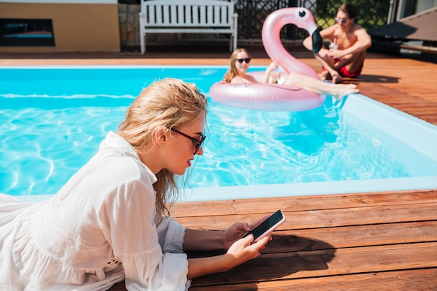 Seitlich frau, die ihr telefon am pool überprüft