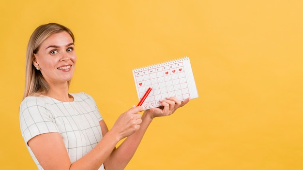 Seitlich frau, die ihren menstruationskalender zeigt