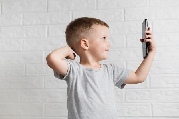 Seitlich kleiner junge, der ein selfie nimmt
