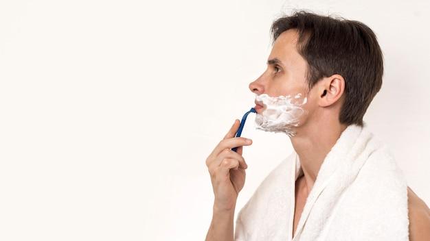 Seitlich mann, der mit exemplarplatz sich rasiert