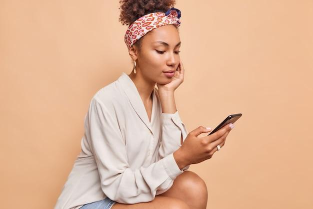 Seitliche aufnahme eines hübschen dunkelhäutigen teenager-mädchens liest kommentare unter post in sozialen netzwerken