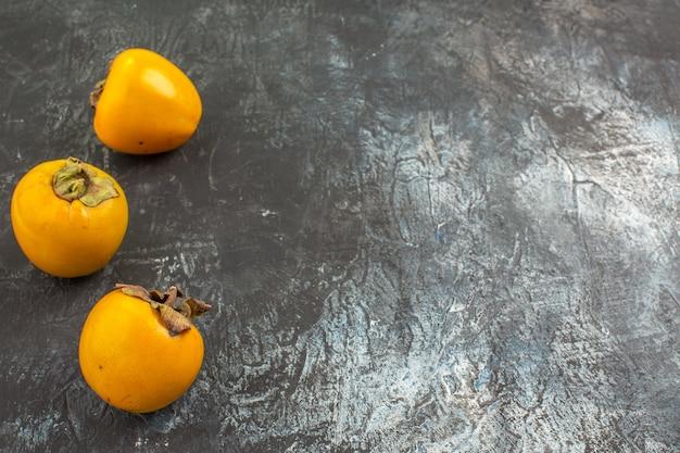 Seitliche nahansicht persimmons die appetitlichen kakis auf dem grauen hintergrund