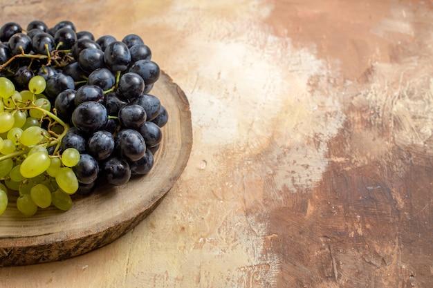 Seitliche nahansicht weintrauben von schwarzen und grünen trauben auf dem schneidebrett