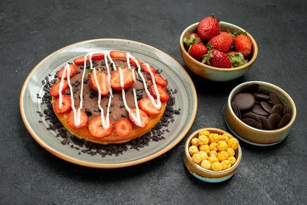 Seitliche nahaufnahme appetitlicher kuchen weißer kuchenteller mit schokolade und erdbeere und schalen mit schokoladenerdbeere und haselnuss auf dunklem tisch