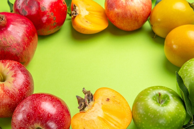Seitliche nahaufnahme bunte früchte granatapfel äpfel kaki und blätter auf dem tisch
