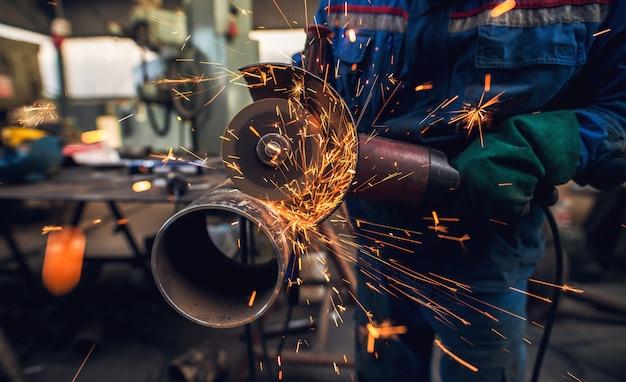 Seitliche nahaufnahme des professionellen fleißigen mannes in uniform schneidet metallrohrskulptur mit einem großen elektrischen schleifer, während funken in der industriellen stoffwerkstatt oder in der garage fliegen.