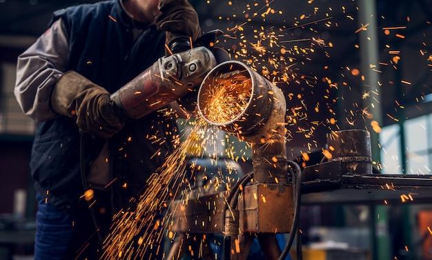 Seitliche nahaufnahme des professionellen fokussierten arbeiters in uniform, die an der metallrohrskulptur mit einem elektrischen schleifer arbeitet, während funken in der industriellen stoffwerkstatt fliegen.