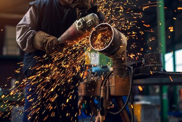 Seitliche nahaufnahme des professionellen fokussierten fleißigen mannes in der uniform, die an der metallrohrskulptur mit einem elektrischen schleifer arbeitet, während funken in der industriellen stoffwerkstatt fliegen.