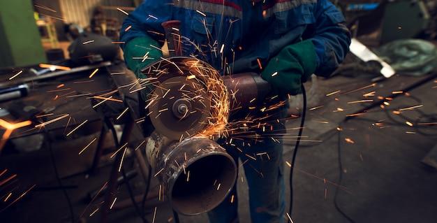 Seitliche nahaufnahme des professionellen fokussierten fleißigen mannes in uniform schneidet metallrohrskulptur mit einem großen elektrischen schleifer, während funken in der industriellen stoffwerkstatt fliegen.