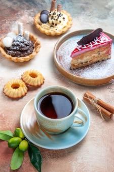 Seitliche nahaufnahme eine tasse tee eine tasse tee cupcakes kekse zimtkuchen zitrusfrüchte