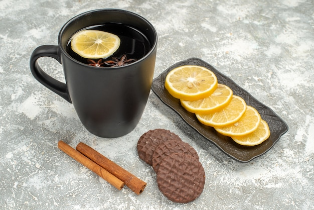 Seitliche nahaufnahme eine tasse tee eine tasse tee zimtstangen kekse zitronenscheiben