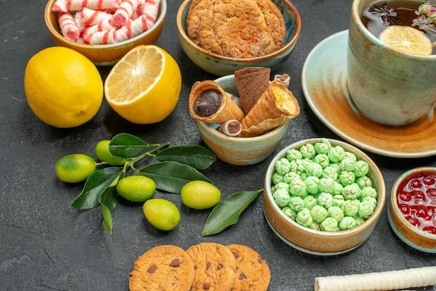 Seitliche nahaufnahme eine tasse tee zitrusfrüchte eine tasse kräutertee kekse marmelade süßigkeiten