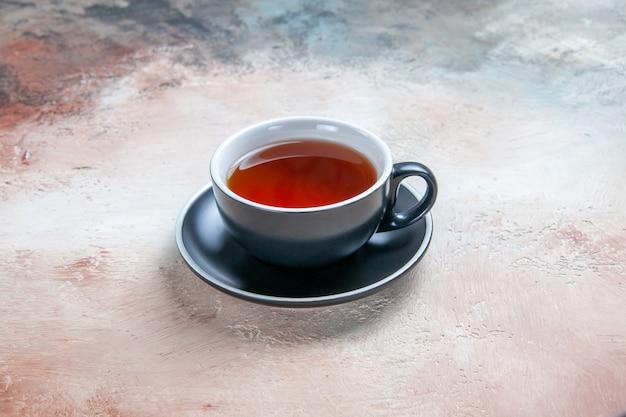 Seitliche nahaufnahme einer tasse tee schwarze tasse tee auf dem tisch