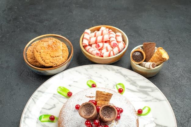 Seitliche nahaufnahme eines kuchens ein kuchen mit roten johannisbeeren waffeln schalen mit süßigkeiten