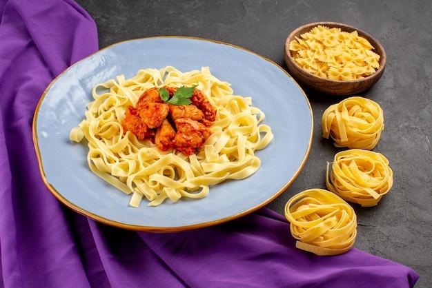 Seitliche nahaufnahme pasta mit soße teller einer appetitlichen pasta mit soße und fleisch neben den schüsseln pasta auf der lila tischdecke