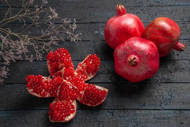 Seitliche nahaufnahme reife granatäpfel reifer gepillter granatapfel zwischen ästen und drei granatäpfel auf dunklem hintergrund