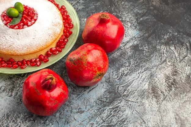 Seitliche nahaufnahme rote granatäpfel drei rote granatäpfel neben dem appetitlichen kuchen