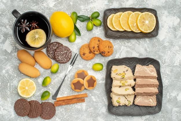 Seitliche nahaufnahme süßigkeiten eine tasse tee gabel die appetitlichen kekse süßigkeiten und zitrusfrüchte