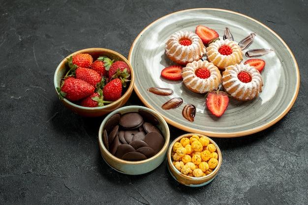 Seitliche nahaufnahme süßigkeiten und kekse appetitliche kekse mit erdbeere und schalen mit haselnüssen schokolade und erdbeere auf schwarzem tisch
