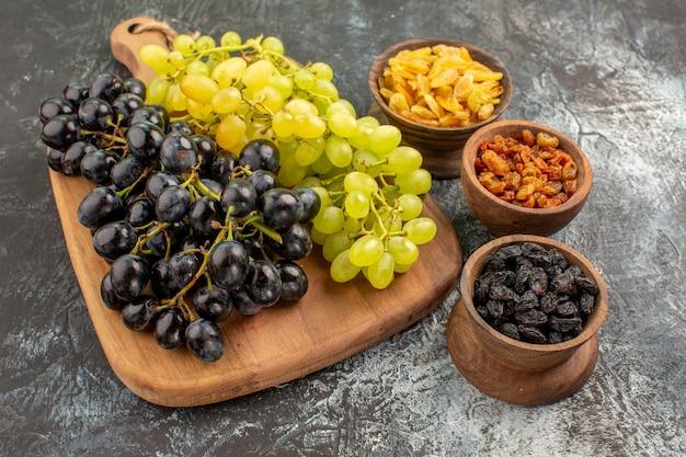 Seitliche nahaufnahme trauben drei schüsseln mit getrockneten früchten leckere trauben auf dem schneidebrett