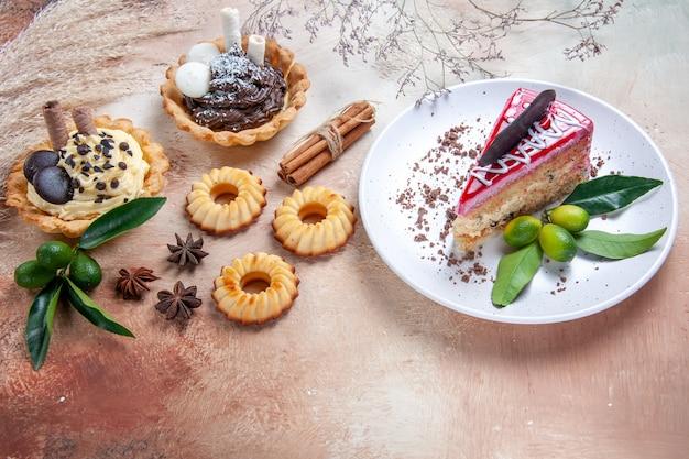 Seitliche nahaufnahme versüßt einen kuchen mit schokoladencupcakes, keksen, zitrusfrüchten, zimt