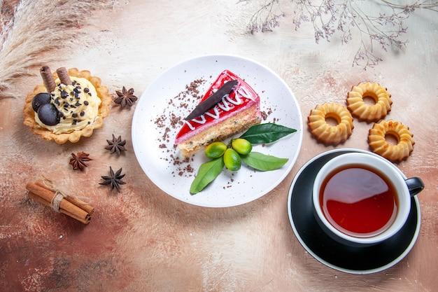 Seitliche nahaufnahmeansicht ein kuchenteller mit kuchenplätzchen cupcakes eine tasse tee zitrusfrüchte sternanis