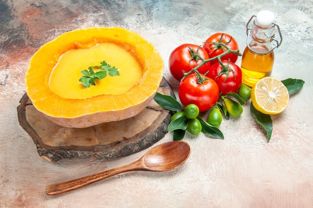 Seitliche nahaufnahmeansicht suppenlöffel tomaten zitrusfrüchte öl kürbissuppe auf dem brett