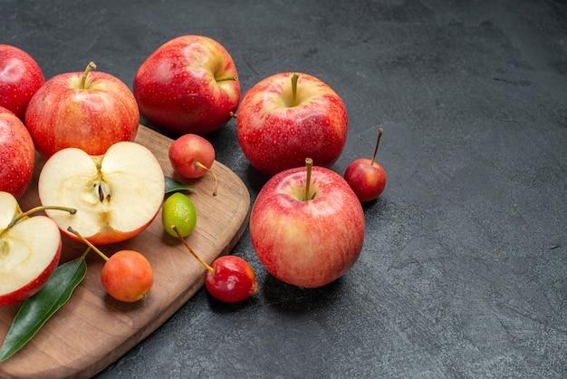Seitliche nahaufnahmefrüchte früchte früchte beeren auf dem brett neben den äpfeln mit blättern