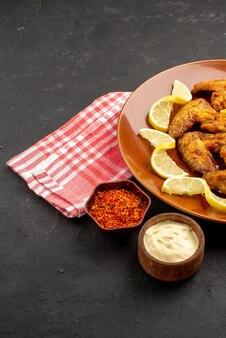 Seitlicher nahaufnahmeteller mit fastfood chicken wings pommes frites mit zitrone und schüsseln mit saucen und gewürzen auf rosa-weiß karierter tischdecke auf der rechten seite des schwarzen tisches