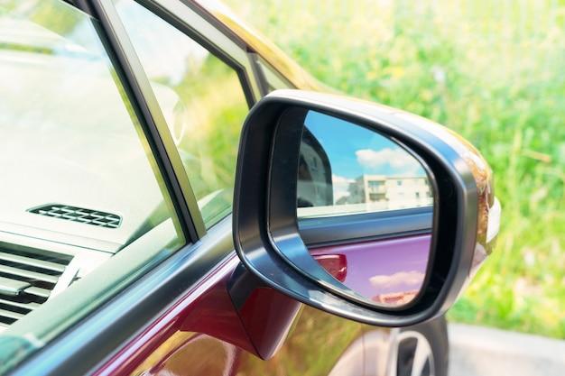Seitlicher rückspiegel an einem modernen roten auto