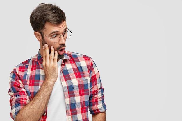 Seitlicher schuss eines betäubten jungen europäischen mannes mit borsten, schaut verwirrt zur seite und bemerkt etwas seltsames