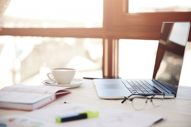 Seitlicher vordergrund eines arbeitsschreibtisches mit dem laptop, dem tasse kaffee, den brillen und dem briefpapier