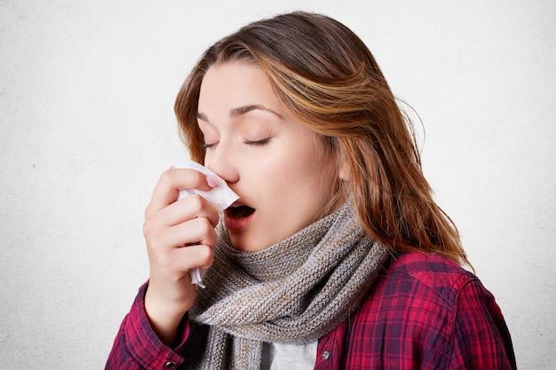 Seitliches porträt der jungen frau hat allergische rhinitis, niest in serviette, hat kopfschmerzen, trägt schal am hals, isoliert über weißer wand. konzept für krankheit, saisonale viren und gesundheitsprobleme